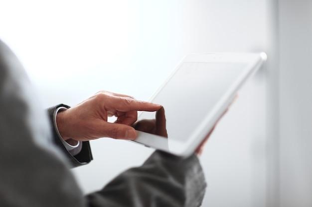 クローズアップ。ぼやけた画像のビジネスマンがデジタルタブレットの画面を押す。コピースペースのある写真