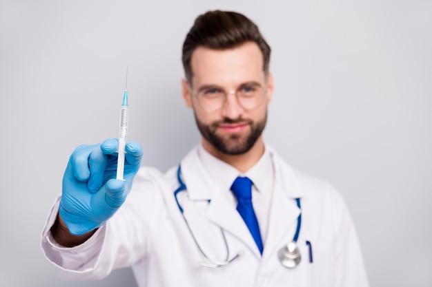 Крупный план размытого портрета его симпатичного привлекательного опытного квалифицированного бородатого врача фельдшера, готовящегося, показывая антивирусный препарат укола, изолированный на светло-белом сером пастельном цвете