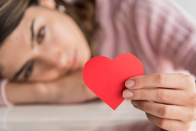 Close-up blurred woman holding heart Free Photo