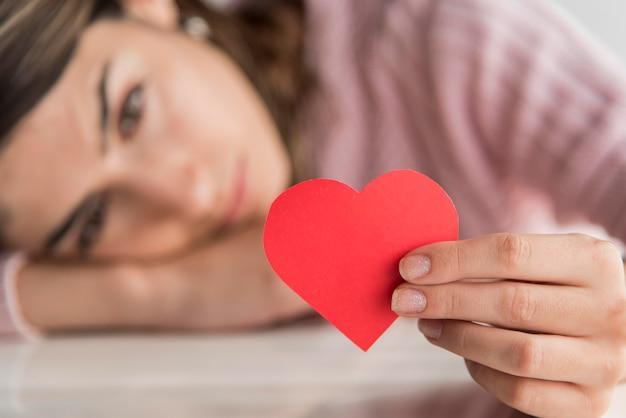 Крупным планом размыты женщина держит сердце