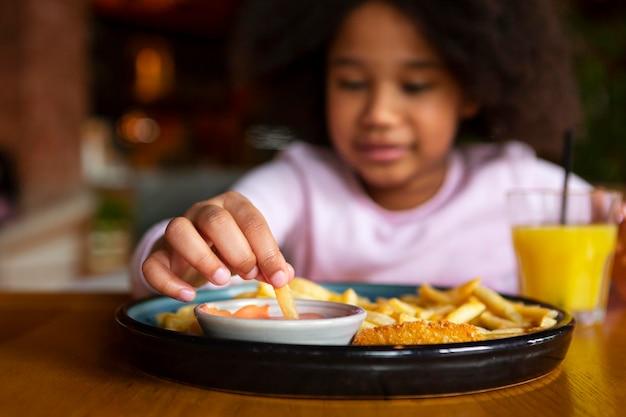 Chiuda sulla ragazza sfocata che mangia patatine fritte