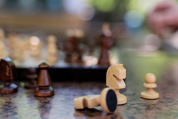 Primo piano mano sfocata e pezzi degli scacchi