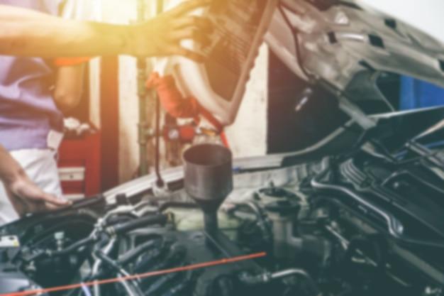 店内で車のエンジンを扱っている修理工のぼやけた手をクローズアップ。車の修理ステーションと車のメンテナンス。