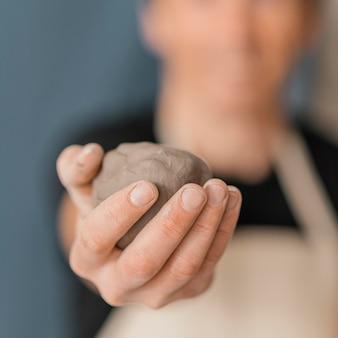 Крупным планом размыто человек, держащий глину