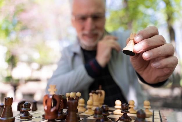 Primo piano sfocato vecchio che gioca a scacchi