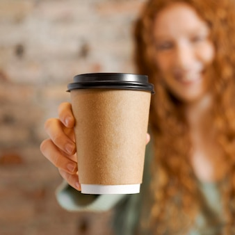 Close up blurry woman holding cup