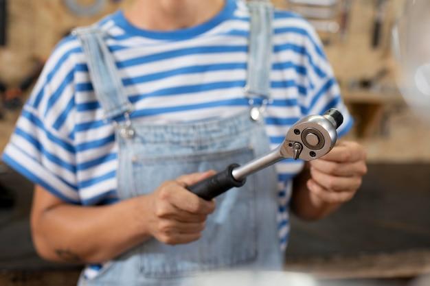 Закройте размытый рабочий, держащий инструмент