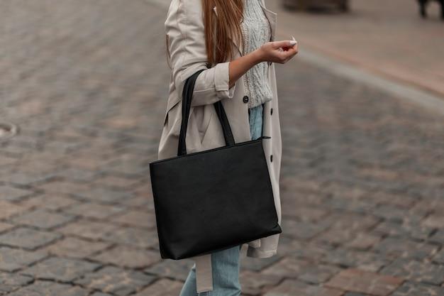 スタイリッシュな黒革のバッグでヴィンテージニットセーターの若い女性の体をクローズアップ