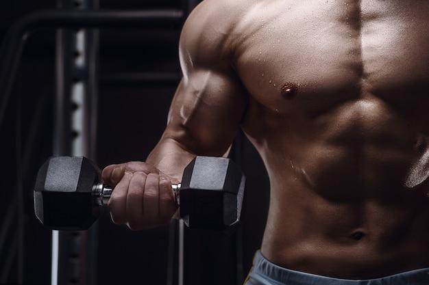 ジムでアスリートの男の体をクローズアップボディービルフィットネスとスポーツのコンセプト