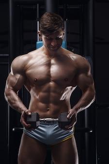 ジムでアスリートの男の体をクローズアップボディービルフィットネスとスポーツのコンセプト Premium写真