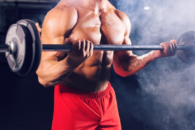 Close up of bodybuilder doing the exercises with barbell. strong male with naked torso on dark