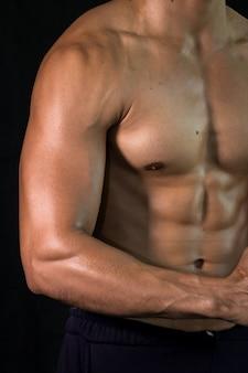 Close up bodybuilder muscular beautiful body on black background