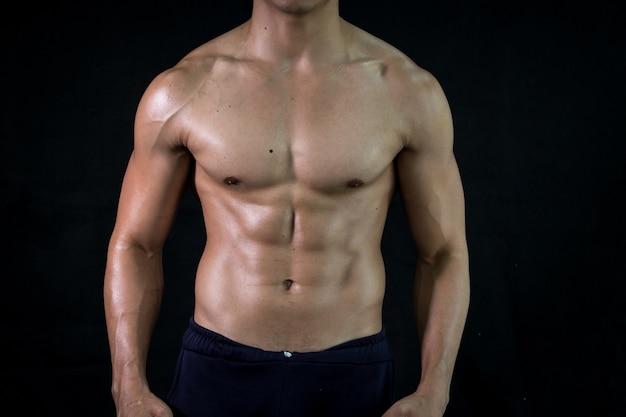 Крупным планом культурист мышечной красивые тела на черном фоне