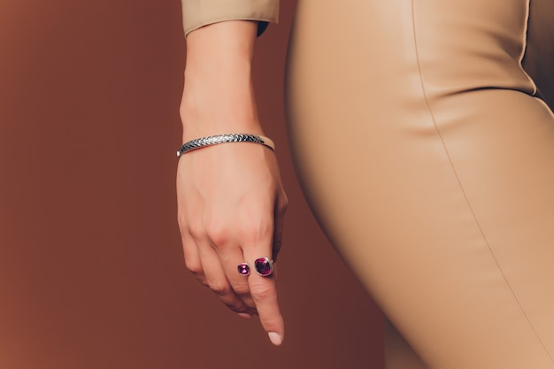 Close up of boho styled woman hands with silver jewelry.