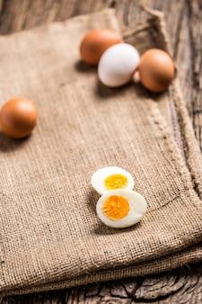木の板にゆで卵または生の鶏卵をクローズアップ。