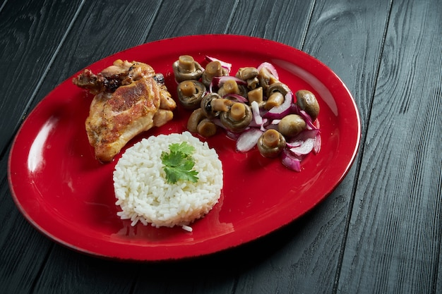 Close up on boiled rice with pickled mushrooms and chicken on a red plate on a black wooden table. healthy food for diet