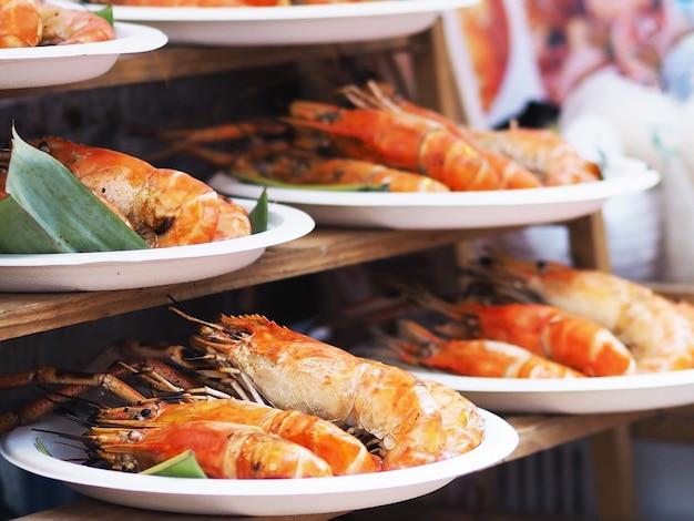 Закройте вареные креветки, готовые к употреблению, над белыми тарелками на вынос, присутствующими на деревянной полке на рынке выходного дня.