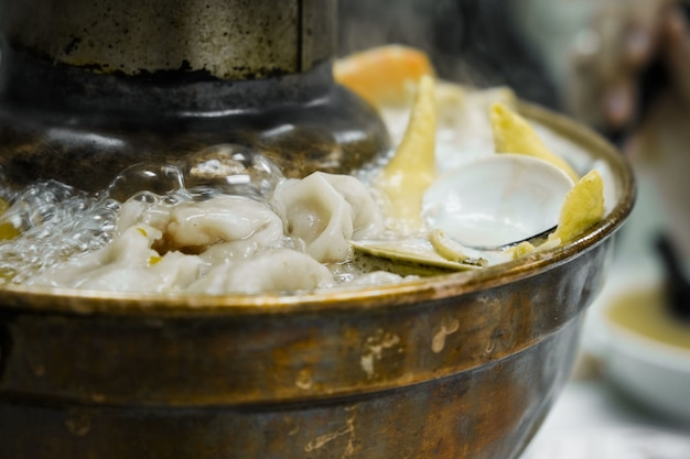 Close-up boiling oysters and dumplings in pot