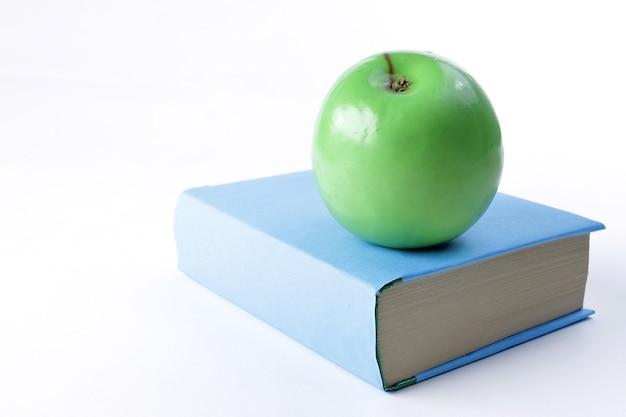 Закройте вверх. книга и зеленое яблоко на белом фоне.