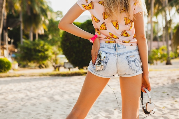 Close up booty in shorts of attractive hipster woman on beach in stylish colorful outfit on sunny summer tropical vacation holding accessories cap sunglasses headphones view from back
