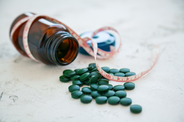 Close-up bottle of green spirulina pills with a tape-measure. super food concept. spirulina dietary supplement.