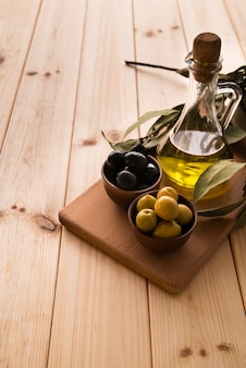 Close-up bottle of olive oil and olives