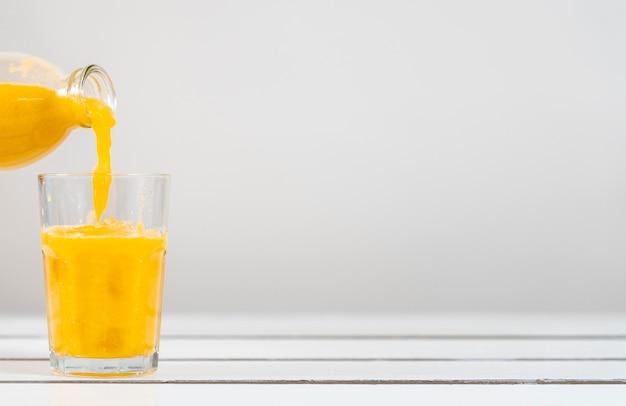 Bottiglia del primo piano che versa il succo in vetro