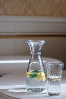 Close-up of a bottle with a cap and a glass of water with mint and lemonon a white table and sun glare