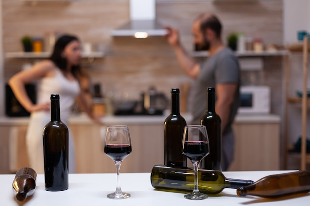 Close up of bottles and glasses filled with wine, liquor, booze and alcoholic beverage for alcohol addicts in background chatting. intoxicated drunk people with unhealthy addiction