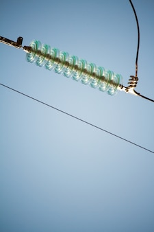 Close-up bottom view of insulators on high-voltage wires on a power tower against a blue sky