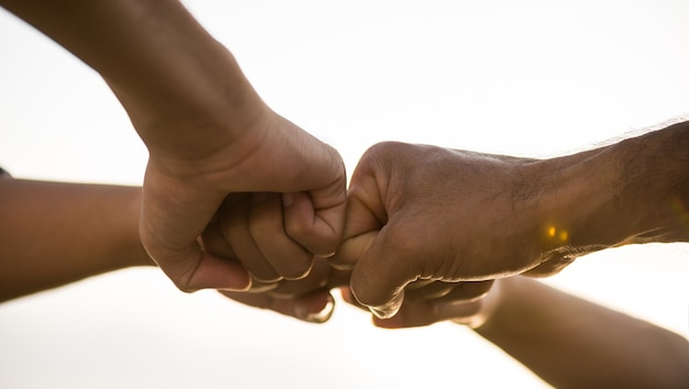 Close up bottom view of people giving fist bump showing unity and teamwork
