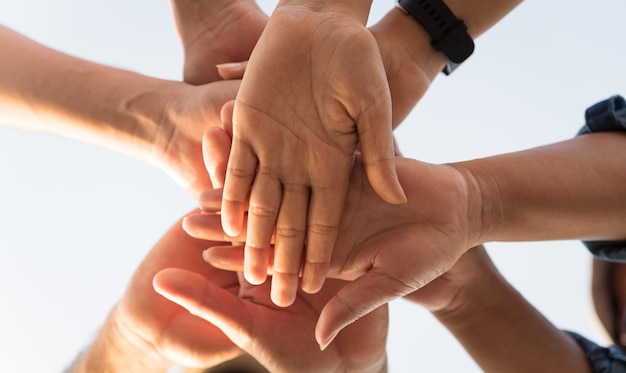 Close up bottom view of people putting their hands together friends with stack of hands showing unity and teamwork