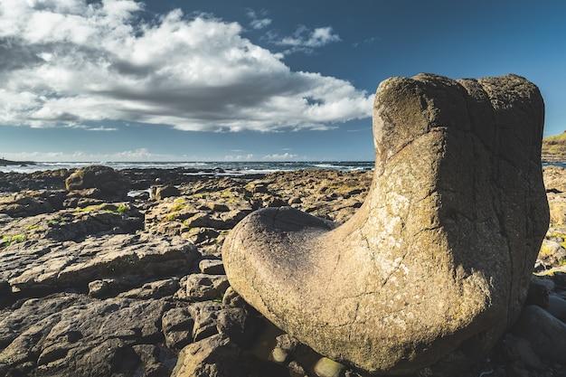 Валун крупным планом на каменном пляже. облачно дождливое небо фон. береговая линия северной ирландии. залитый солнцем гладкий большой камень на каменной поверхности острова. горизонтальный вид. потрясающий ирландский пейзаж.
