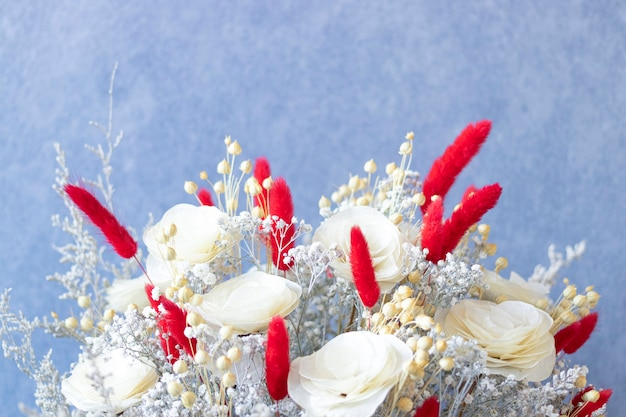 Close up on bouquet of colorful dried flowers and white roses