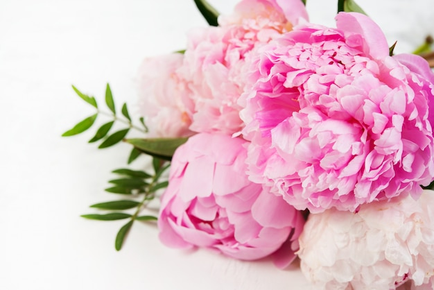 Close up bouquet of fresh beautiful flowers lies on a white background. pink peonies lie on the right . horizontal photo