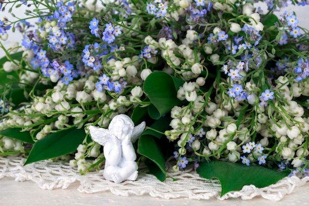 Close up of a bouquet of lilies of the valley and forget me nots and a white angel