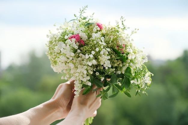 신선한 꽃 장미와 은방울꽃의 클로즈업 꽃다발이 여성의 손에 있습니다. 봄날, 휴일, 결혼식, 아름다움