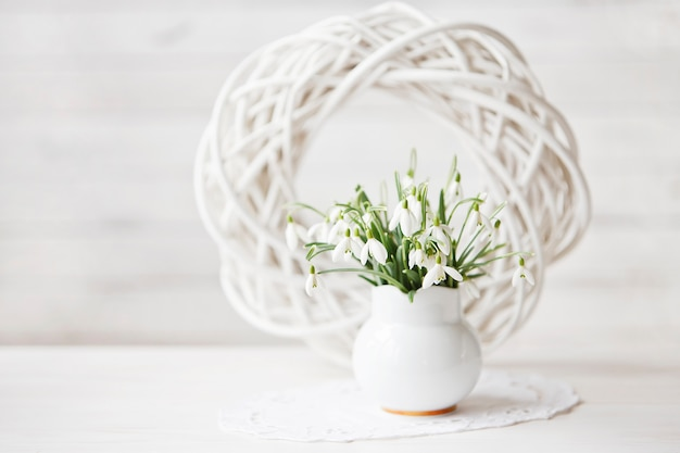 Close-up of a bouquet of spring flowers of snowdrops on a white wooden background.