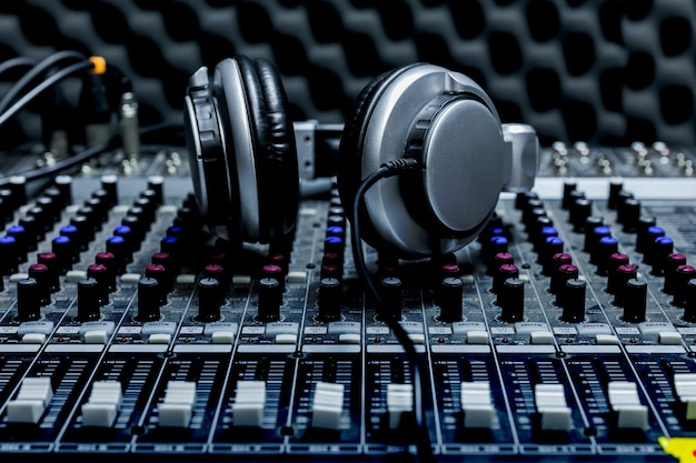 Close-up of boutique recording studio control desk, dj headphones for professional disc,  equipment for sound recording studio, mixer and dj headphones