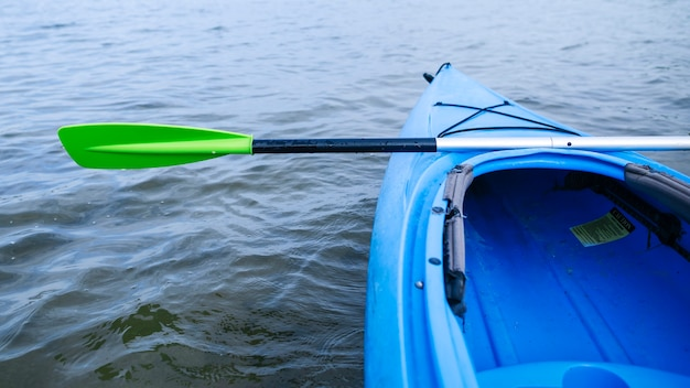 Close-up of the bow of a kayak heading out onto a still lake