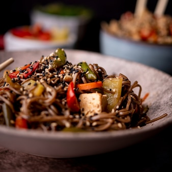 Close-up of bowl of noodles with sesame seeds and vegetables