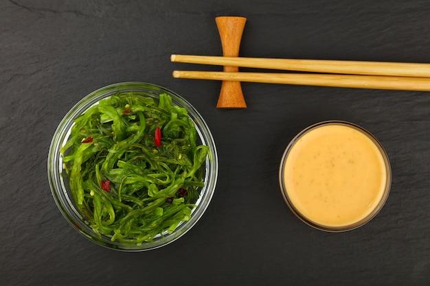 Закройте миску зеленого салата из водорослей вакаме с соусом сатай и палочками для еды на фоне черной грифельной доски, вид сверху, прямо над