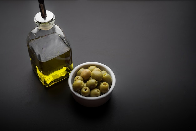 Close-up of bowl of olives and olive oil on kitchen worktop
