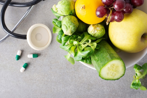 Close-up bowl with fruits and vegetables and pills