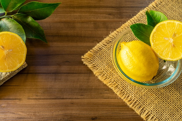 Close up of bowl with lemon and green leaves on rustic wooden