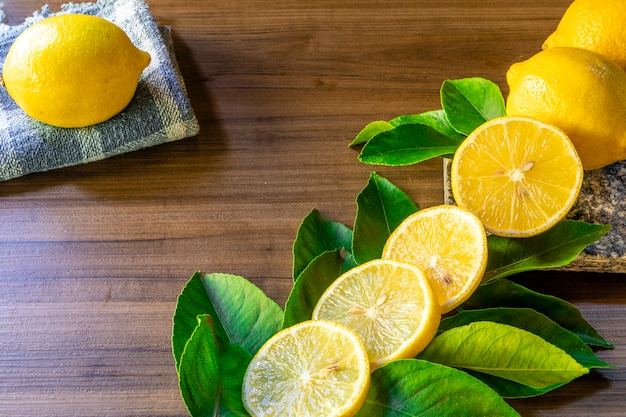 Close up of bowl with lemons and green leaves on rustic wooden surface