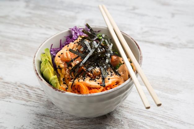 Close-up of bowl with salmon poke, typical hawaiian salad.