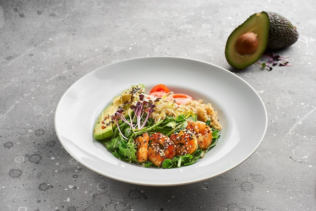 Close-up, bowl with tiger prawns, quinoa and avocado and olive oil on gray stone