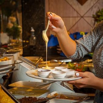 Крупным планом миски со сладкими соусами медом, джемом, шоколадной пастой, сгущенным молоком на белой тарелке