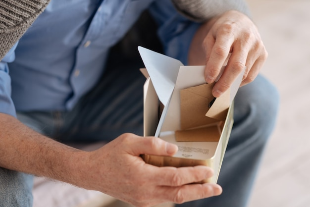 Close up of a box filled with old letters while being in hands of a nice sad elderly man